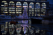 Christmas tree lit up at night with coloured lights on St Katherine Docks in London, England, United Kingdom. St Katharine Docks, in the London Borough of Tower Hamlets, were one of the commercial docks serving London, on the north side of the river. They were part of the Port of London, in the area now known as the Docklands, and are now a popular housing and leisure complex. Here it is now a central mooring for boats and yachts.