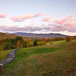 A stone wall in a hay field in Sugar Hill, New Hampshire. The Franconia Range in the White Mountains is in the distance. Sunset.