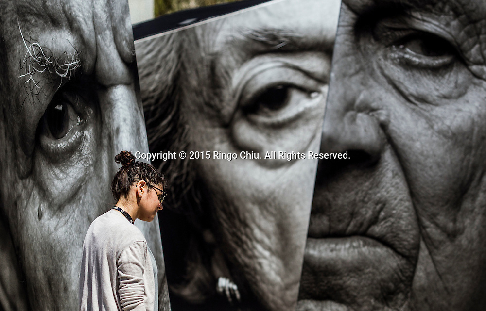 A visitor gets a closer look at an outdoor installation called iWitness, a grouping of 20 larger-than-life 3-D photo sculptures of Armenians survivors, at the Music Center Plaza and Grand Park  in downtown Los Angeles on Monday, April 27, 2015. The exhibit is part of events memorializing the centenary of the 1915 killings of an estimated 1.5 million Armenians during the Ottoman Empire rule of Turkey, while elsewhere in Los Angeles demonstrators pressed for recognition by Turkey and the U.S. that it was genocide.
