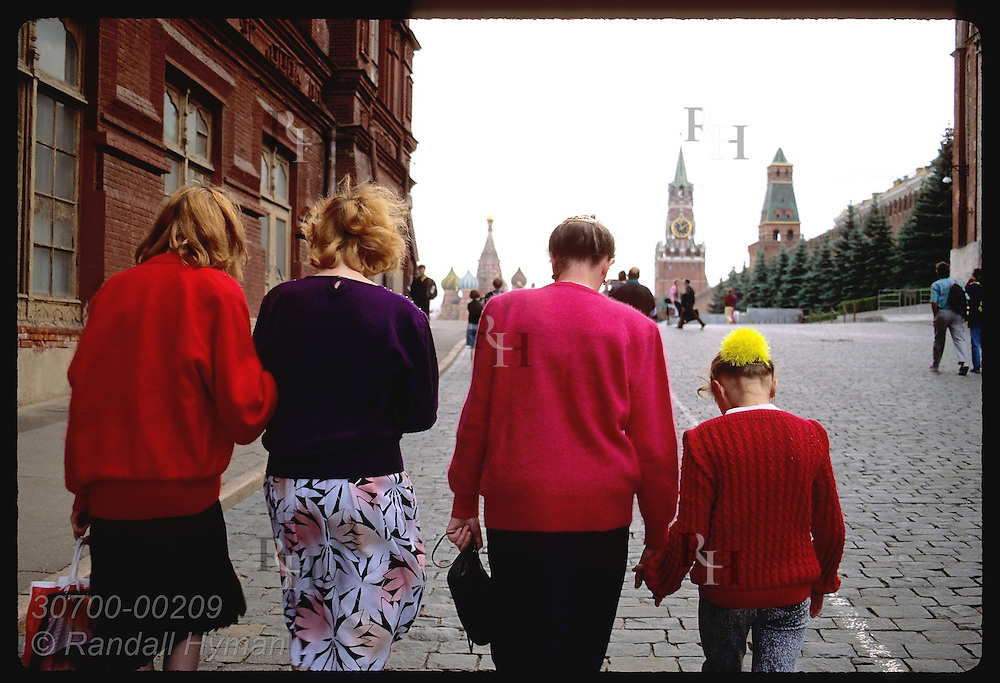 Three women and young girl walk together up side street to Red Square on June day in Moscow. Russia