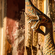 A carved wooden Nāga (or serpent deity) that forms part of the exterior wall at Wat Si Saket in Vientiane, Laos. Built in 1818, the temple is of the Siamese style rather than the traditional Lao style. It is now perhaps the oldest temple still standing in Vientiane.