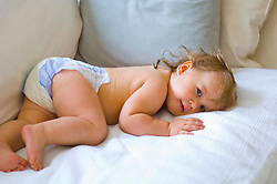 Blonde baby in pampers lying on a white sofa