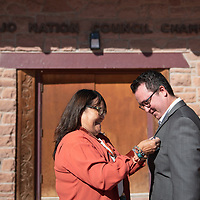 Faith Roessel, left, fastens a Council Delegate pin to her son Carl Roessel Slater's jacket after he is sworn in to the 24th Navajo Nation Council as the Council Delegate for the Tsaile/Wheatfields, Lukachukai, Round Rock, Tséch'izhí and Rock Point Chapters at the Navajo Nation Council Chamber October 10 in Window Rock.
