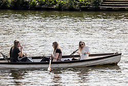 Licensed to London News Pictures. 18/04/2021. London, UK. Rowers enjoy a drink and soak up the sunshine along the Thames at Richmond, South West London on the first weekend of the easing of Covid-19 restrictions. Shops, pubs, bars and restaurants are now serving customers for the first time in over 4 months as a mini heatwave is set to hit the UK this week with temperatures predicted to reach up to 18c in London and the South East. Photo credit: Alex Lentati/LNP