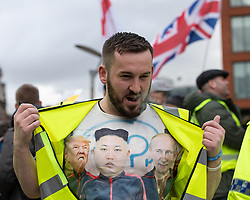 "© Licensed to London News Pictures . 09/02/2019. Manchester , UK . JAMES GODDARD shows a t-shirt depicting Donald Trump , Kim Jong Un and Vladimir Putin at a"" Yellow Vest "" protest in Piccadilly Gardens in Manchester City Centre . The yellow vest concept has been adopted from French demonstrators by some British groups in support of Brexit , Donald Trump and former EDL leader Stephen Yaxley-Lennon - aka Tommy Robinson . A similar demonstration in the city in January was ridiculed after protesters were kettled by police in front of a branch of Greggs the Baker . Photo credit : Joel Goodman/LNP"