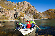 Men navigate a small boat onto shore along the rugged coastline of Vaeroy Island, Lofoten Islands, Norway.