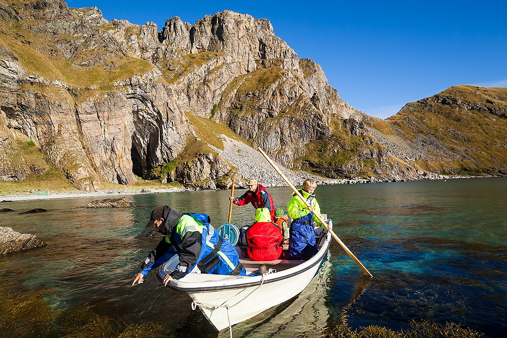 Men navigate a small boat onto shore along the rugged coastline of Vaeroy Island, Lofoten Islands, Norway.