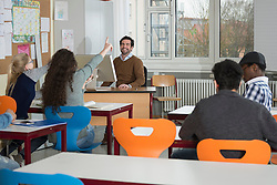 Happy teacher in school with dedicated students in a classroom School, Bavaria, Germany