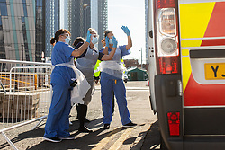 © Licensed to London News Pictures . 21/04/2020. Manchester, UK. Hospital staff wave goodbye to one of the first patients to be discharged from the hospital as an ambulance takes him home . The National Health Service has built a 648 bed field hospital for the treatment of Covid-19 patients , at the historical railway station terminus which now forms the main hall of the Manchester Central Convention Centre . The facility is treating patients from across the North West of England , providing them with general medical care and oxygen therapy after discharge from Intensive Care Units . Photo credit : Joel Goodman/LNP