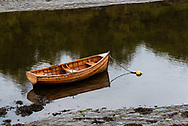 A lone rowboat is anchored in shallow muddy waters.