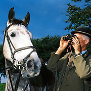 A follower wearing a tweed jacket and bowler hat stands with his horse whilst watching the Devon and Somerset Staghounds, Exmoor, Somerset, UK. Stag hunting is an activity involving the tracking, chase and sometimes killing of a stag by trained hounds and a group of followers lead by a 'master' who follow the hounds on foot or on horseback. This controversial sport, was banned in England and Wales in November 2004.
