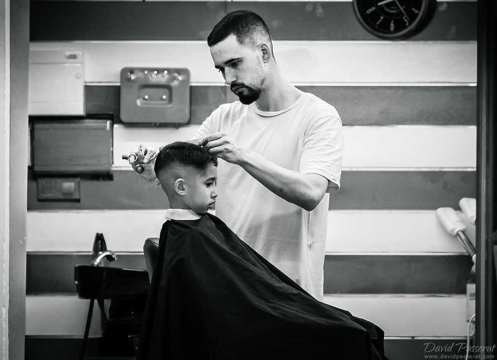 Hairdresser giving a haircut to a boy.