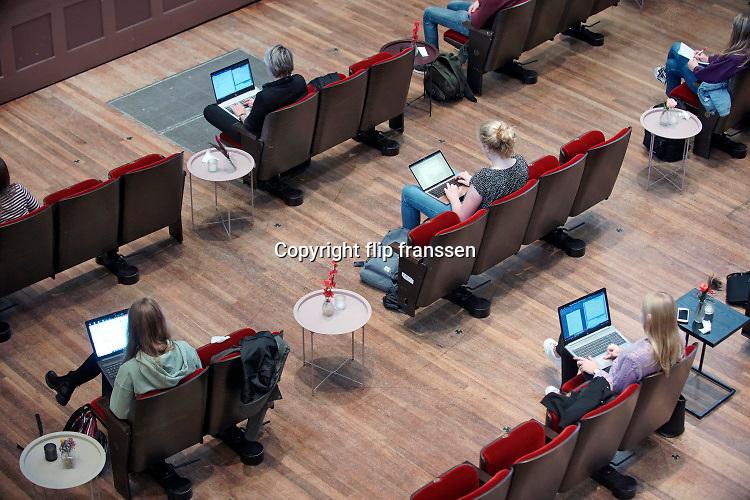 Nederland, Nijmegen, 1-10-2020  NIET GEBRUIKEN BIJ BERICHTEN OVER STUDENTEN ALS COROABRON/ VERSPREIDERS. De Radboud universiteit biedt colleges aan in concertgebouw de Vereeniging. Hierdoor kunnen studenten toch fysiek en coronaproof onderwijs volgen . Het hoorcollege wordt ook nog gestreamd . Hier een college sociale wetenschappen, pedagogiek . Het personeel van de zaal heeft de stoelen op afstand van elkaar en een beetje gezellig met een bloemetje neergezet. De meeste studenten hebben een laptop .Foto: ANP/ Hollandse Hoogte/ Flip Franssen