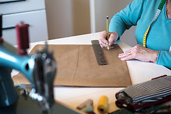 Old woman drawing pattern on sewing desk
