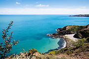 Views across the North Coast of Jersey from the cliff tops, looking down towards Vicard Harbour, a small pebbly bay hidden amongst the cliffs and surrounded by calm turquoise water