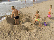 children digging in beach sand