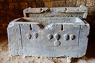Tripoli, Lebanon - September 7, 2010: A stone sarcophagus, probably Phoenician, with relief carvings of faces on the side. It is in the Citadel in Tripoli, Lebanon.