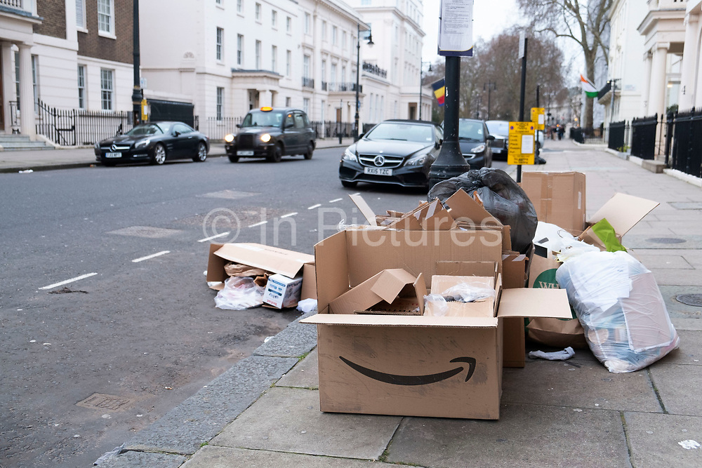 Empty Amazon pacakging makes a mess put out as rubbish for recycling in Belgravia, London, United Kingdom.