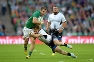 Darren Cave of Ireland is tackled by Florin Surugiu of Romania..Rugby World Cup 2015 pool D match, Ireland v Romania at Wembley Stadium in London on Sunday 27th September 2015.<br /> pic by John Patrick Fletcher, Andrew Orchard sports photography.