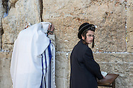 """Morning prayer at the Western Wall. A man fully covered in a tallit shawl, with an arm tefillin wrapped on his right hand. A boy wears the head tefillin, or """"shel rosh"""", placed above the forehead. The Torah commands that this set of small black leather boxes containing scrolls of parchment inscribed with verses from the Torah,  should be worn to serve as a sign and remembrance that God brought the children of Israel out of Egypt. """"And it shall be for a sign for you upon your hand, and for a memorial between your eyes, that the law of the LORD may be in your mouth; for with a strong hand did the LORD bring you out of Egypt.<br /> —Exodus 13:9"""""""