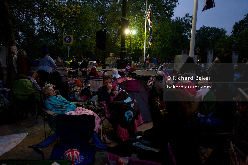 Royalist enthusiasts camp outdoors in the Mall, in the hours before the royal marriage of Prince William and Kate Middleton. Dawn light reveals a massed crowd of Britons and foreign visitors (many Americans and Commonwealth citizens)  who are asleep in small tents and warm under sleeping bags. Taking place on Friday 30th April in front of millions the crowds are already gathering to claim their ideal locations in the front rows along the procession route later that morning.