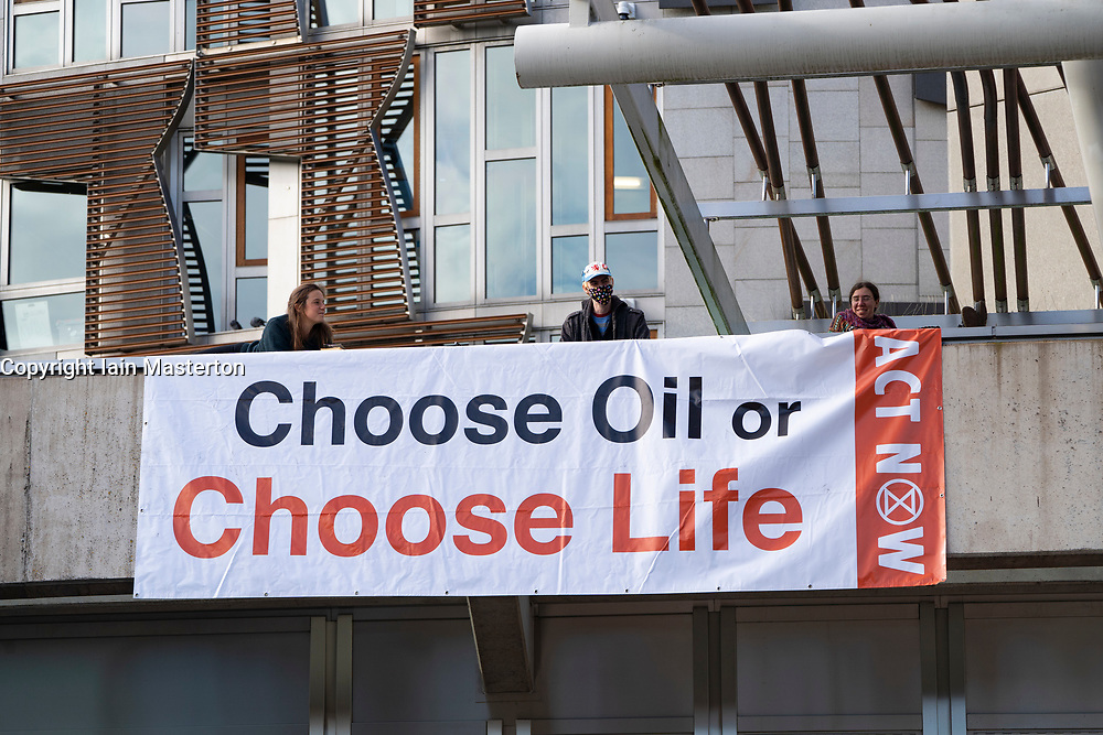 "Edinburgh, Scotland, UK. 8 October 2020. Extinction Rebellion stage protest on roof of Scottish Parliament building at Holyrood in Edinburgh.  The group, Extinction Rebellion Scotland have hung a banner reading ""Choose Oil or Choose Life""  in a protest against fossil fuels. Iain Masterton/Alamy Live News"