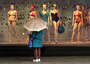 A shopper in downtown Seattle checks out swimsuits in a Nordstrom window during a rain shower. <br />