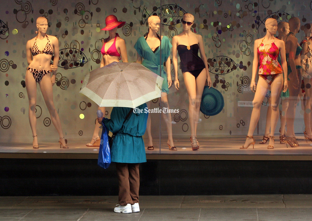 A shopper in downtown Seattle checks out swimsuits in a Nordstrom window during a rain shower. <br /> Ellen Banner / The Seattle Times