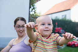 Mother is amazed about her baby son's on first steps, Munich, Bavaria, Germany