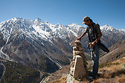 An Indian man on top of a mountain places a rock on a trig point on 20th October 2009, Himachal Pradesh, India. The region of Spiti and Kinnaur is a remote and tribal area of the Indian Himalayas near the Tibetan border.