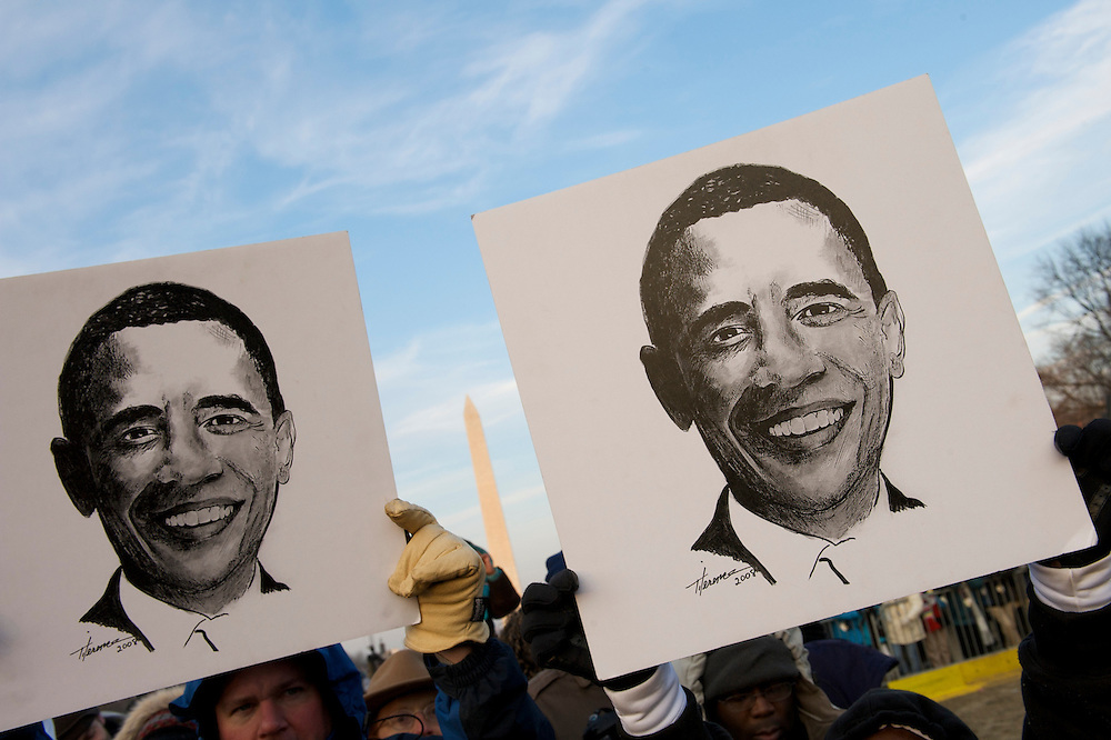 Barack Obama supporters wave hand drawn sketches of his visage on the day of his historic Presidential inauguration.  An estimated two million people flocked to Washington D.C. for the ceremony, enduring freezing temperatures to witness Obama take the oath of office becoming the first African-American to become President, the 44th in the history of the United States of America.