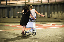 © Licensed to London News Pictures . 26/08/2016 . Manchester , UK . A woman pushes a man across the road on an airport baggage trolley . Revellers in Manchcester's Gay Village for 2016 Manchester Gay Pride Big Weekend . Photo credit : Joel Goodman/LNP