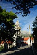 Belltower of the Dominican Church and Monastery of Saint Nicholas (Sveti Nikola), viewed from tree-lined road. Island of Korcula, Croatia