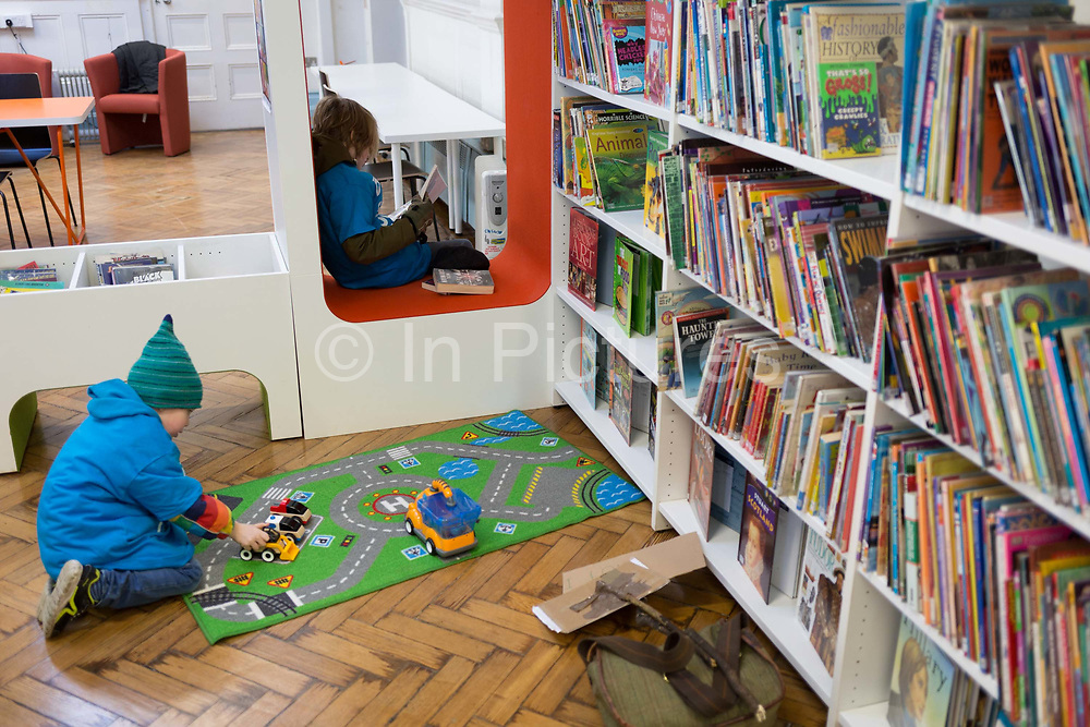 A young reader in the re-opened Carnegie Library on Herne Hill in south London which has opened its doors for the first time in almost 2 years, on 15th February 2018, in London, England. Closed by Lambeth council and occupied by protesters for 10 days in 2016, the library bequeathed by US philanthropist Andrew Carnegie has been locked ever since because, say Lambeth austerity cuts are necessary. A gym that locals say they dont want or need has been installed in the listed basement and actual library space a fraction as before and its believed no qualified librarians will be present to administer it. Protesters also believe this community building will ultimately sold off by Lambeth council for luxury homes.