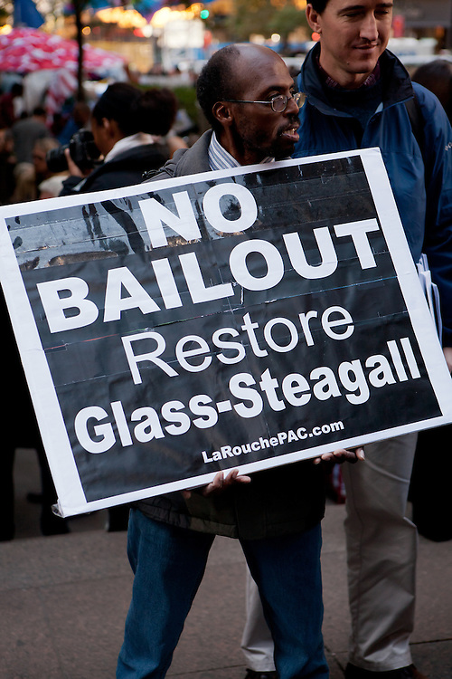 """An African-American man from the LaRouche PAC carries a large sign reading """"No bailout restore Glass-Steagall"""""""