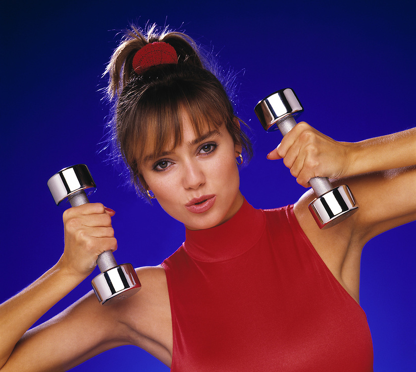 Beautiful woman exercising with silver dumbbells against a blue background. She is wearing a red turtleneck top.
