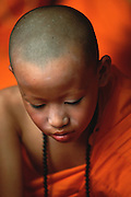 A novice monk just after he has been ordained at Poy Sang Long, the yearly ordination ceremonies in Mae Hong Son, Thailand, in April 2003. The boy still has some makeup left in his face from when he was earlier dressed up as a prince in memory of the Buddha. Practically every Shan boy goes through the Poy Sang Long sometime between the age of eight and fourteen. After the ordination, the boy spends about one month in a Buddhist monastery, and then he usually returns to normal life again.