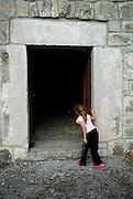 Child (5 years old) looking into dark interior of Church of Sveti Stjepana (Saint Stephen), Rascane, Croatia