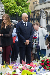 Parliament Square, Westminster, London, June 17th 2016. Following the murder of Jo Cox MP friends and members of the public lay flowers, light candles and leave notes of condolence and love in Parliament Square, opposite the House of Commons. PICTURED: State for Business Secretary Sajid Javid pauses in contemplation after laying flowers.