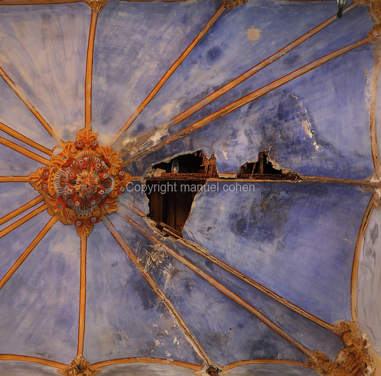 Looking up at a beautiful decorated ceiling badly damaged with damp patches and a hole, in an abandoned building in a state of dereliction in the old town or Casc Antic of Tortosa, Tarragona, Spain. Tortosa is an ancient town situated on the Ebro Delta which has a rich heritage dating from Roman times. In recent years, many buildings in the old town have been abandoned and fallen into disrepair. Picture by Manuel Cohen