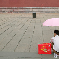 Asia, China, Beijing, Young Chinese man sits in shade of umbrella in open plaza near the Gate of Heavenly Peace in the Forbidden City.