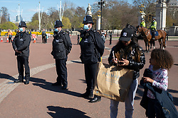 © Licensed to London News Pictures.17/04/2021. London, UK. Police officers take part in a minute's silence to commemorate the death of the Duke of Edinburgh Prince Philip outside Buckingham Palace. The funeral is taking place in Windsor Castle today. Photo credit: George Cracknell Wright/LNP