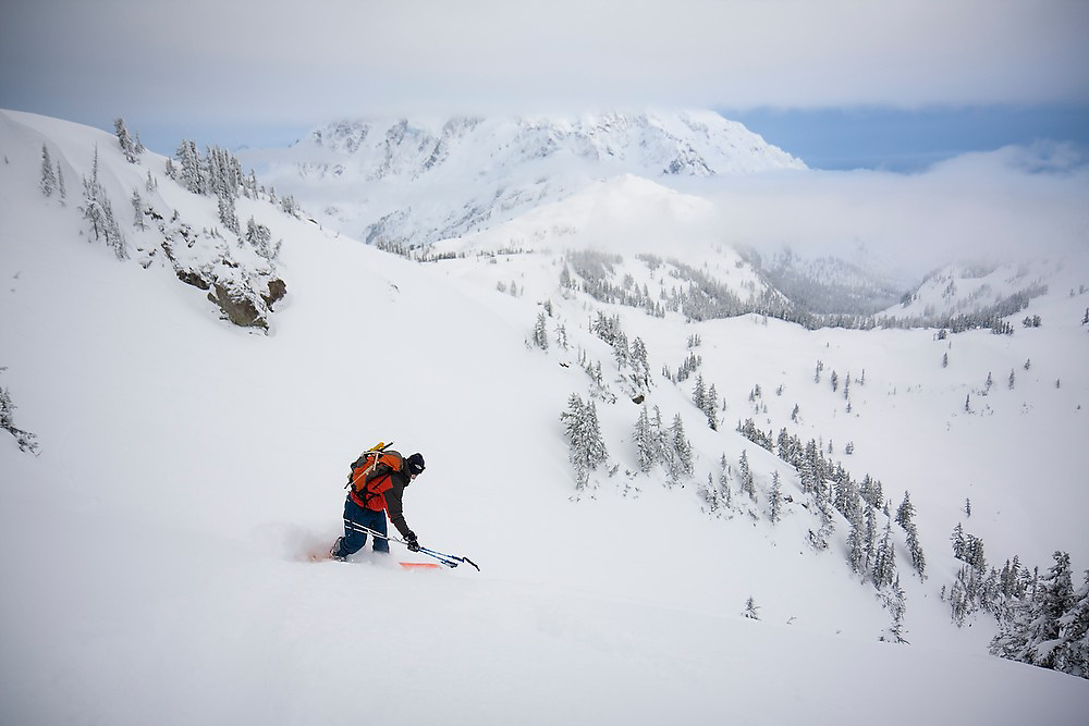 Splitboarder Rok Roskar links together turns through deep powder in the backcountry, Mount Baker-Snoqualmie National Forest, Washington. Mount Baker is visible in the background.