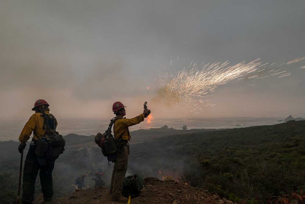 Firefighters light a controlled burn around a house on Highway 1 to help fight the Dolan Fire near Jolon, Calif. on Sept. 13, 2020.