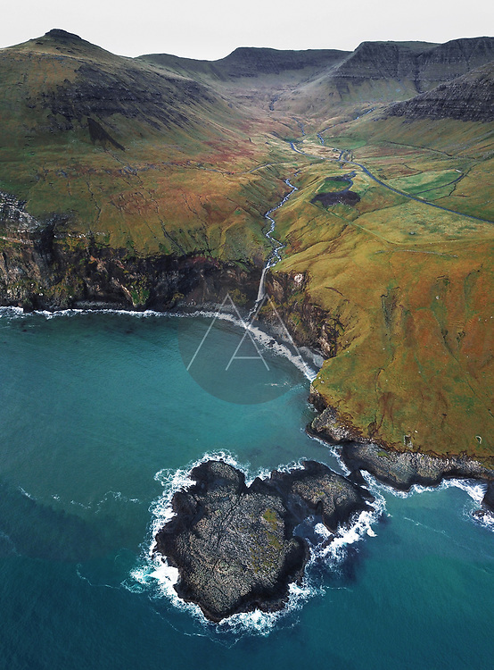 Aerial view of mountain waterfall Skarðsáfossur flowing into the Atlantic Ocean surrounded by mountains on Vágar in the Faroe Islands, Denmark