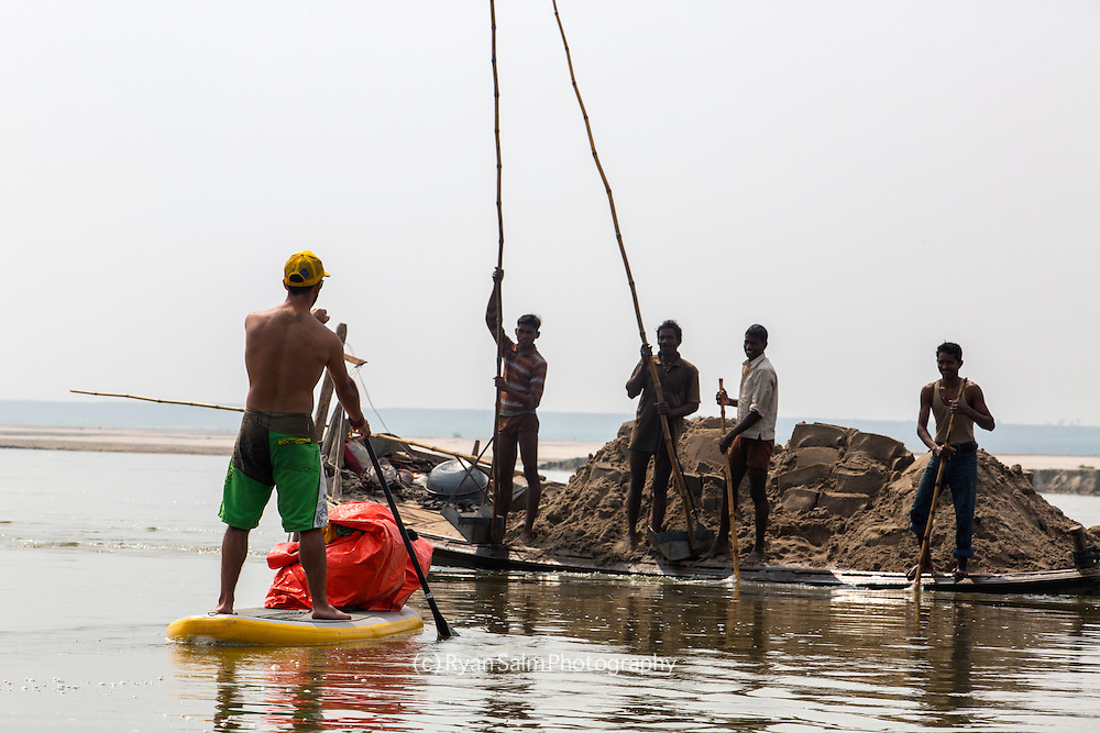 A crew of local men gather mud from the river as a strange man approaches on a SUP.