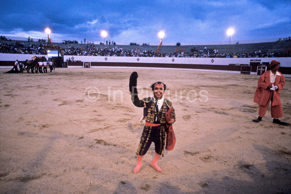 Bullfighting dwarf Guillermo Gomez waves to the public at the end of intense day of bullfighting bull steers, Cienpozuelo, Spain.