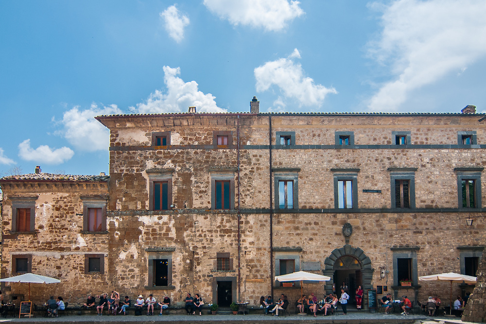 """Tourists enjoy a sunny day in San Donato square in Civita di Bagnoregio.<br /> Civita di Bagnoregio is a town in the Province of Viterbo in central Italy, a suburb of the comune of Bagnoregio, 1 kilometre (0.6 mi) east from it. It is about 120 kilometres (75 mi) north of Rome. Civita was founded by Etruscans more than 2,500 years ago. Bagnoregio continues as a small but prosperous town, while Civita became known in Italian as La città che muore (""""The Dying Town""""). Civita has only recently been experiencing a tourist revival. The population today varies from about 7 people in winter to more than 100 in summer.The town was placed on the World Monuments Fund's 2006 Watch List of the 100 Most Endangered Sites, because of threats it faces from erosion and unregulated tourism."""