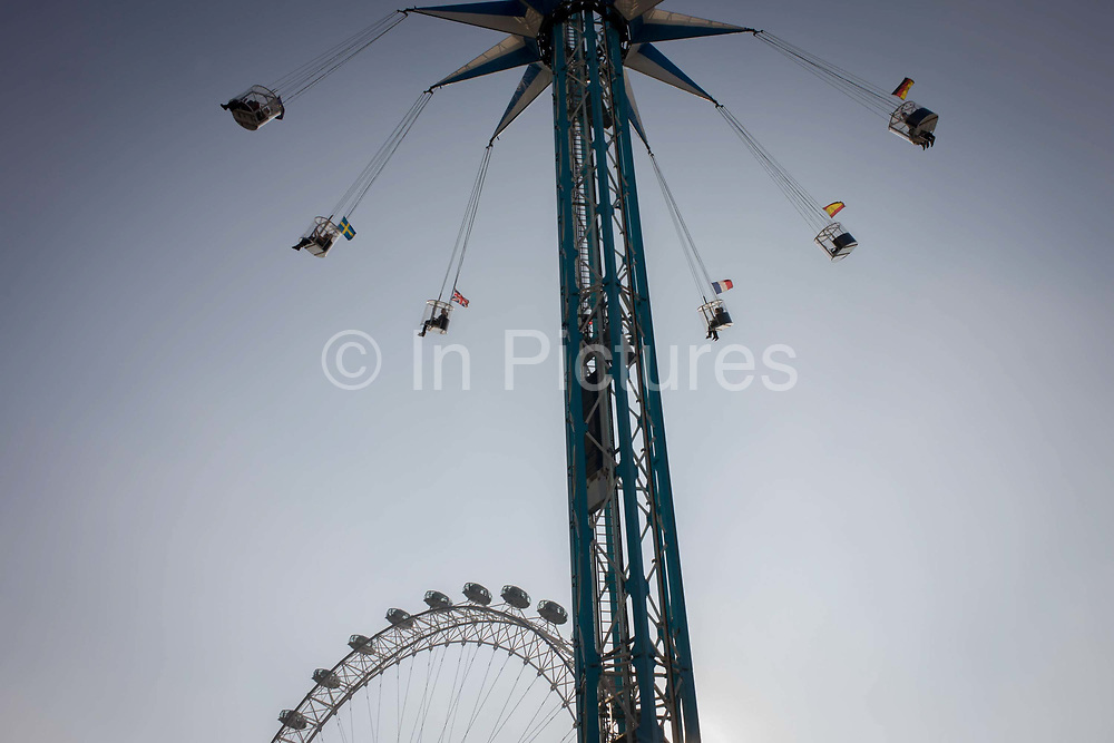 Rising circular fairground ride with EU member flags and Millennium (ferris) Wheel on London's Southbank. Looking up from the ground, we see the theme of circles and silhouettes in an afternoon sky as fearless people on these rides enjoy the scary sensation of flying through the air. Flags of European nations fly from each gondola. The Eye, or as it was known in 2000, the Millennium Wheel, was designed by architects David Blian, Julia Barfield, Malcolm Cook, Mark Sparrowhawk, Steven Chilton and Nic Bailey, and carries 32 sealed, air-conditioned passenger capsules which rotate at 0.26 metres (0.85 feet) per second (about 0.9 km/h or 0.5 mph) so that one revolution takes about 30 minutes.