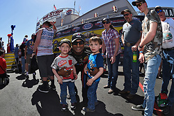 April 8, 2018 - Las Vegas, NV, U.S. - LAS VEGAS, NV - APRIL 08: Antron Brown (4 TF) Don Schumacher Racing (DSR) NHRA Top Fuel Dragster embraces some young fans after walking off the stage for driver intros during the DENSO Spark Plugs NHRA Four-Wide Nationals on April 08, 2018 at The Strip at Las Vegas Motor Speedway in Las Vegas, NV. (Photo by Chris Williams/Icon Sportswire) (Credit Image: © Chris Williams/Icon SMI via ZUMA Press)